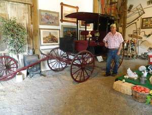 Jack Lawson, co-owner of Lawson's Emu-Z-Um, poses with a 1910 Rockaway Carriage that was used as an elite taxi.